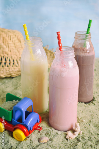 Foto op Plexiglas Milkshake Three bottle of various milkshakes (chocolate, strawberry and vanilla). Healthy smoothie with straw. Tasty milk shake cocktails. Refreshing summer drink on yellow sand summer beach. Copy space