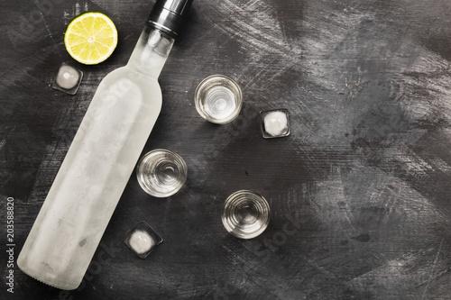 Valokuvatapetti Cold vodka in shot glasses on a black background