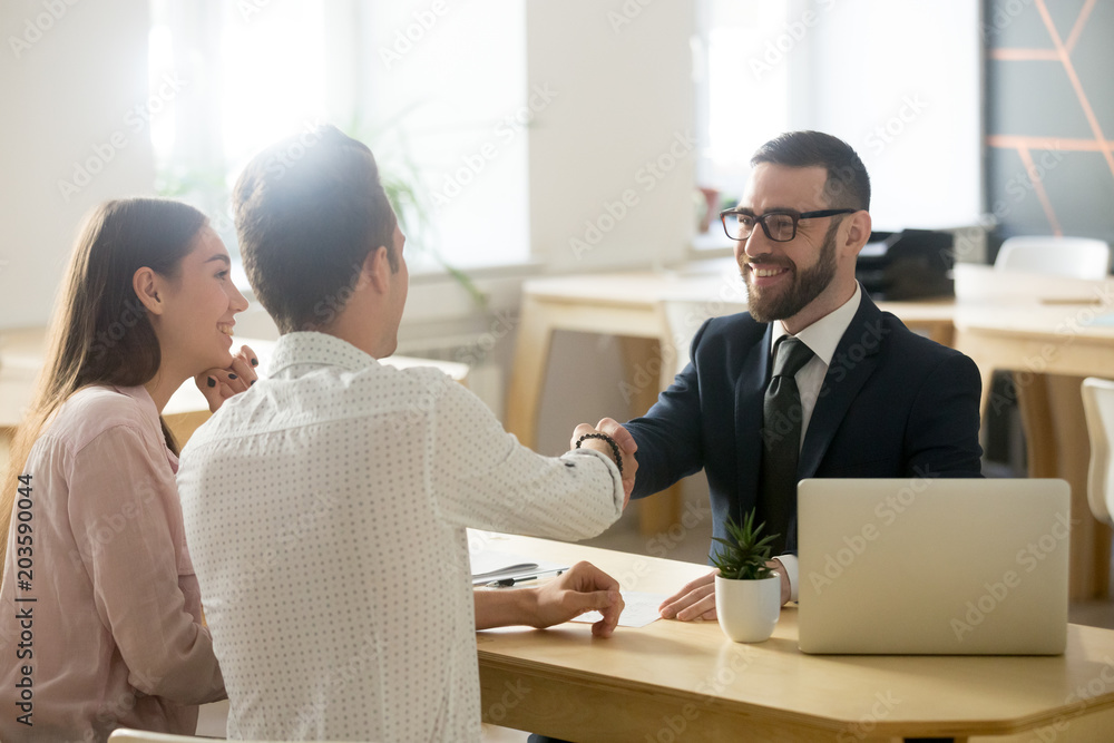 Fototapeta Smiling lawyer, realtor or financial advisor handshaking young couple thanking for advice, insurance broker or bank worker and millennial customers shake hands making deal, investment or taking loan