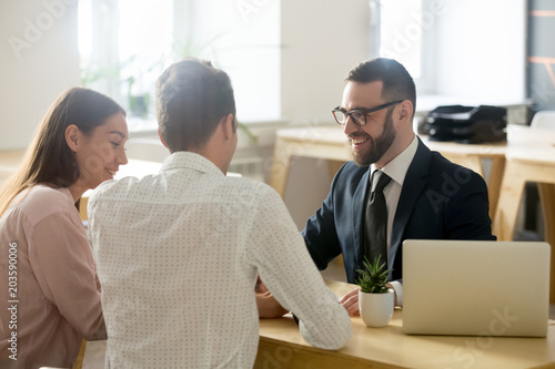 Friendly lawyer or financial advisor in suit consulting young couple, smiling in Fototapete