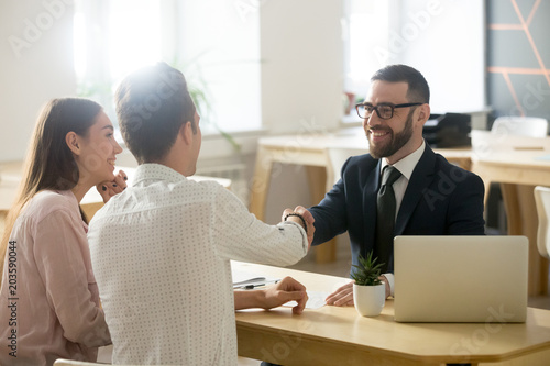 Fotografia Smiling lawyer, realtor or financial advisor handshaking young couple thanking f