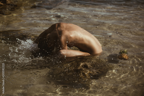 Foto op Aluminium Akt beautiful tanned woman naked relaxing and swimming in water with pineapple. Hot summer day and bright sunny light