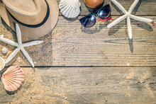 Summer Hat, Shells And Sun Glasses On Wooden And Sandy Background