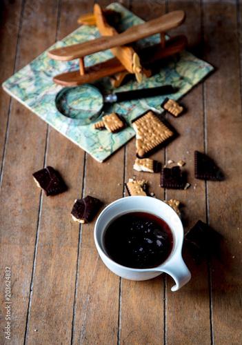 biala-filizanka-z-kawowym-i-drewnianym-samolotem-na-stole
