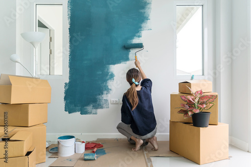 Young asian happy woman painting interior wall with paint roller in new house, Home decoration concept