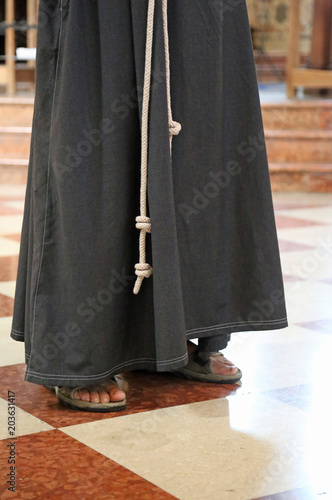 barefoot friar with sandals and brown habit in the cathedral Canvas Print