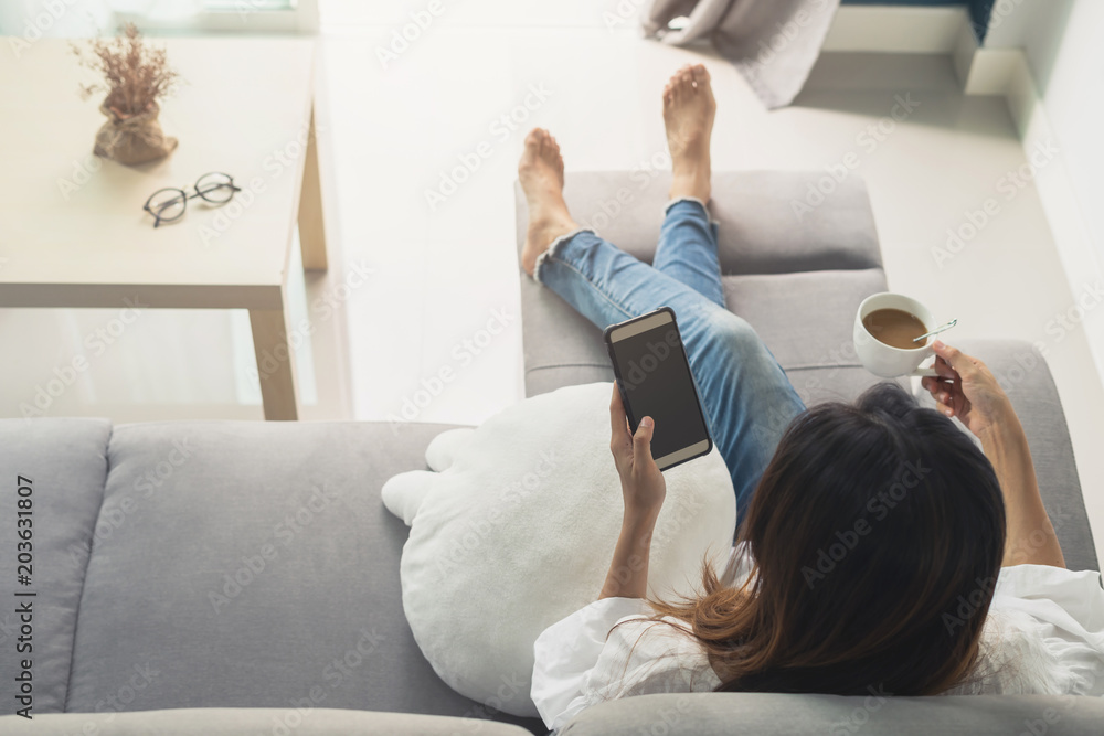 Fototapety, obrazy: Young woman using smartphone at cozy home on sofa in living room