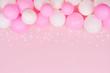 Leinwandbild Motiv Pastel balloons and white confetti on pink background top view. Flat lay style.