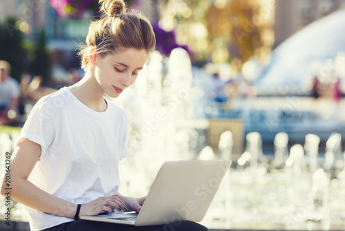 Fotografia  a beautiful teen woman is using her laptop computer outside, while sitting by a