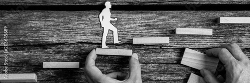 Fotografía  Man holding block as a small silhouette cutouts of a person walks up stairs