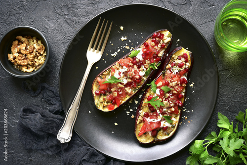 Grilled eggplant stuffed with tomatoes, nuts, pomegranate and yogurt dressing.Top view.