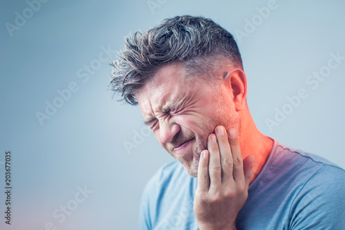 Fotografia  Toothache, medicine, health care concept, Teeth Problem, young man suffering fro