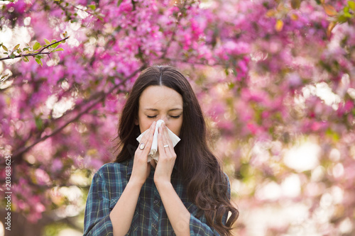Woman blowing nose because of spring pollen allergy Wallpaper Mural