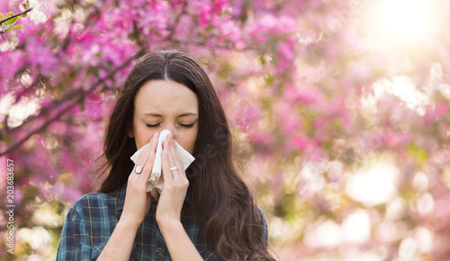 Woman blowing nose because of spring pollen allergy Fototapet
