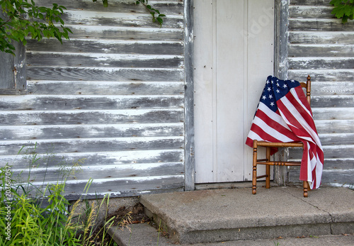 Fotografie, Obraz  American flag draped over old wooden chair by rustic house door