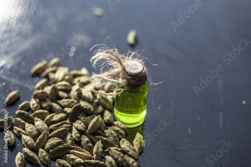 Fototapeta Raw organic green cardamom or elaichi or Elettaria cardamomum or true cardamom with its essence on wooden surface used in many beverages as a flavoring liquid.; obraz