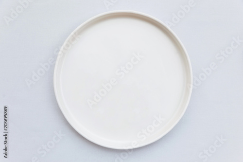 Top view of white empty plate on white tablecloth.
