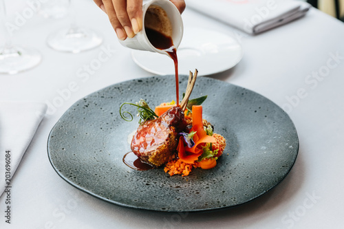 Obraz Modern French cuisine: Roasted Lamb neck & rack served with carrot, yellow curry pouring lamb sauce. Served in black stone plate - fototapety do salonu