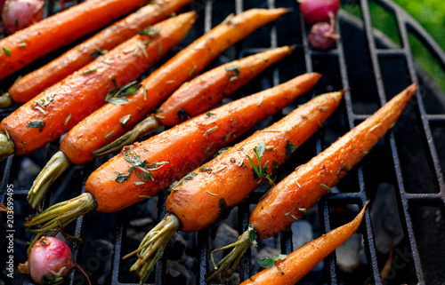 Garden Poster Ready meals Grilled carrots in a herbal marinade on a grill plate, outdoor, top view. Grilled vegetarian food, bbq