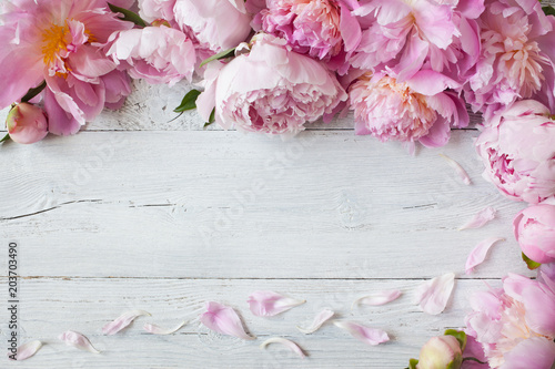 pink peonies on a wooden background for congratulations invitations