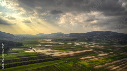 Poster Luchtfoto Aerial view of the green plot fields at Biqat Bet Netofa valley in a cloudy skies day