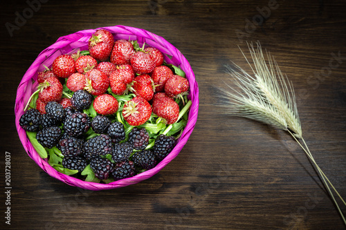 Poster Assortiment Strawberries and blackberries in a colorful basket on an old table. It is a good and fresh fruit that is very healthy and contains few sugars.