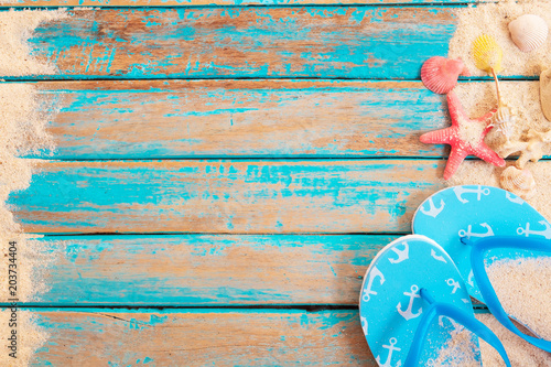 Fotografia  Beach background - top view of beach sand with shells, starfish and slipper on wood plank in blue sea paint color background