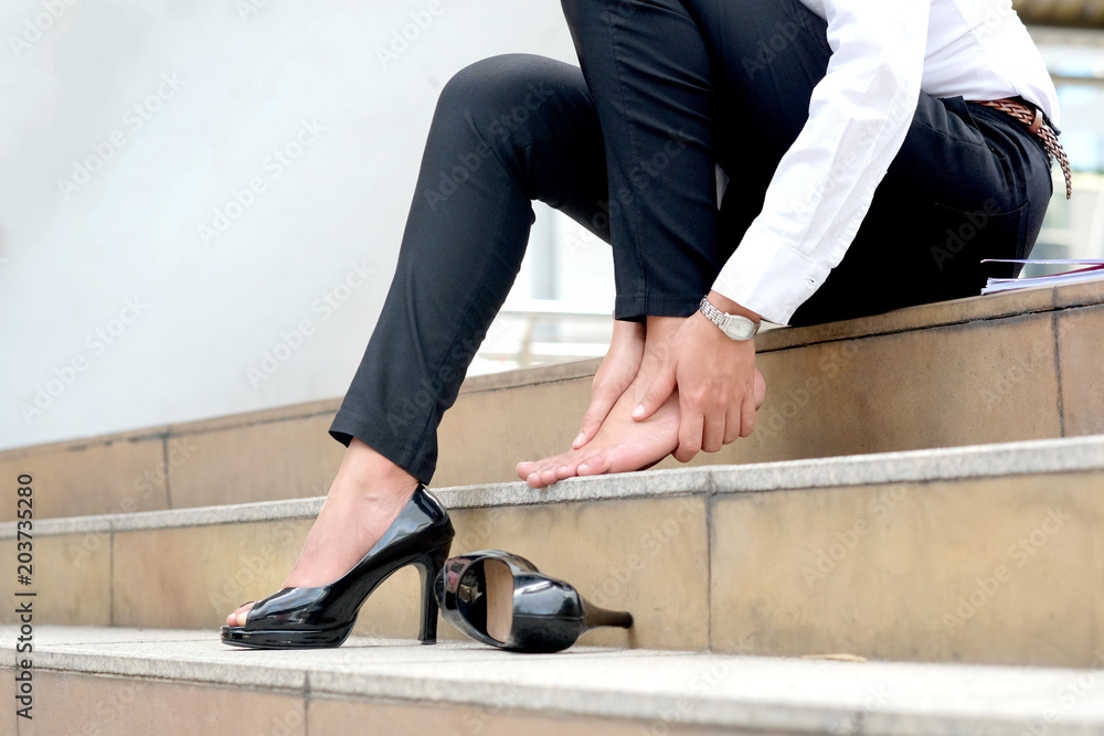 Fototapety, obrazy: Women with leg cramps and ankles from high heels. She sat on the stairs holding her leg.
