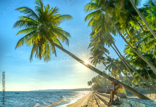 Cadres-photo bureau Palmier Mui Ne, Vietnam - April 21, 2018: The man alone go to end of tropical beach with coconut palm trees as sun gradually create beautiful setting for weekend guests at paradise beach in Mui Ne, Vietnam