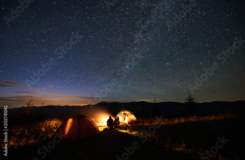 In de dag Kamperen Rear view of silhouette mother and two sons hikers at camping in mountains, sitting on log beside campfire, two tents, looking at amazing night sky full of stars and Milky way, enjoying evening scene