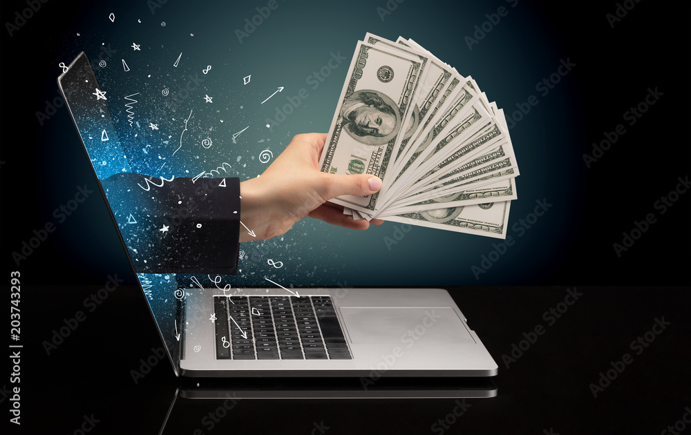 Fototapety, obrazy: Hand with money coming out of a laptop with sparkling effects