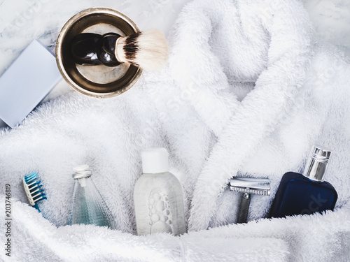 Photo White bathrobe, shaving accessories, lotion aftershave, shampoo, bottle of perfume and piece of lavender soap