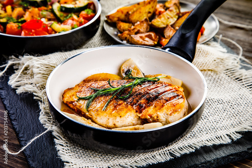 Roast chicken breast with potatoes and vegetables on wooden background