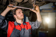 Auto mechanic working at auto repair shop under car with tool