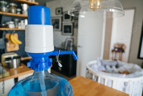 Fotografia, Obraz A larger bottle of clean water 19 liters with blue pomp in the interior of the apartment with a baby cot in the background
