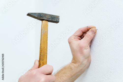 Fotografía  Man's hand  is putting a nail.