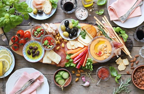 Mediterranean appetizers table concept. Diner table with tapas selection: cured meat and salami, gazpacho soup, jamon, olives, cheese, hummus and vegetables. Overhead view.