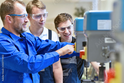 Valokuva  Group of young people in mechanical vocational training with teacher at drilling