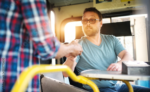 Young bus driver is handing out the ticket to the passenger as they enter the bus.
