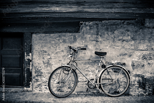 Foto auf AluDibond Modern bicycle standing on an old cobblestone covered street at a rugged stone wall
