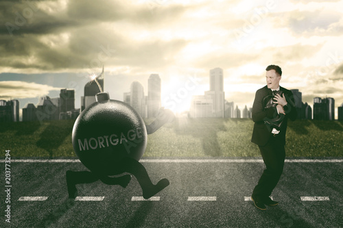 Fotografie, Obraz  Caucasian businessman running away being chased by mortgage