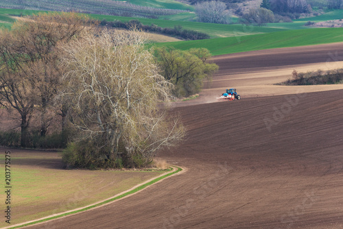 Scenic View Of Farming BlueTractor With Red Harrow Which Plowing And