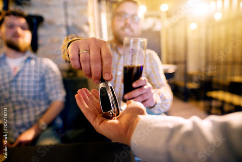 Fototapeta Drunk man with a beer in hand giving car key to the sober friend while enjoying in the bar