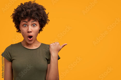 Fotografía  Photo of greatly surprised dark skinned female with bushy Afro haircut, wears casual t shirt, indicates at yellow blank copy space, keeps mouth widely opened, being astonished with something