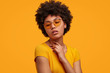 Leinwandbild Motiv Gorgeous dark skinned young female with Afro hairstyle and confident look, poses for fashionable magazine, looks aside thoughtfully, wears trendy shades, poses against yellow studio background