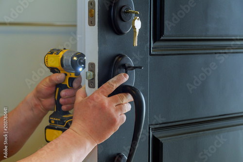 house exterior door with the inside internal parts of the lock visible of a professional locksmith installing or repairing a new deadbolt lock