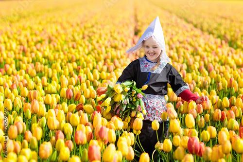 Photo  Child in tulip flower field. Windmill in Holland.