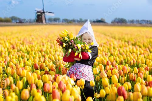 Child in tulip flower field. Windmill in Holland. Canvas-taulu