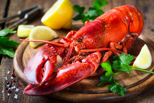 Foto op Plexiglas Schaaldieren Steamed red lobster on a wooden cutting board with parsley and lemon