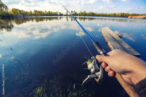 Tuinposter Vissen Fishing with rod on lake